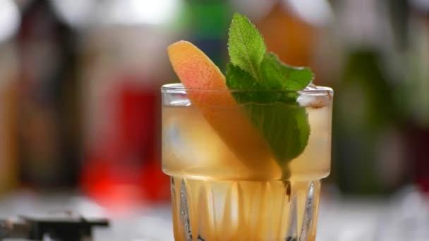 Sklenici pomerančového nápoje se otáčí.