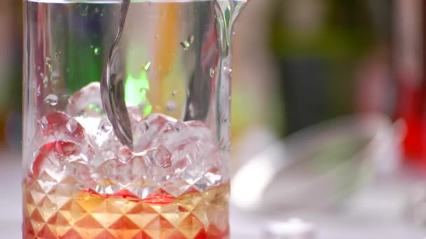 Spoon mixes cocktail in jug.