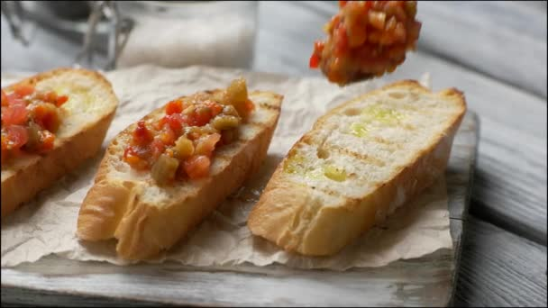 Spoon puts vegetables on bread.