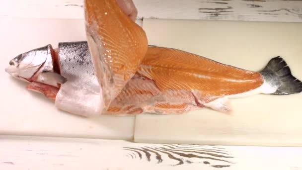 Férfi kezek nyers halakkal.