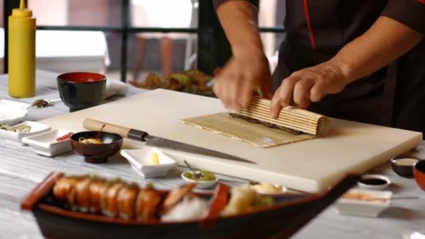 Männliche Hände machen Sushi.