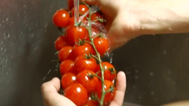 Samec ruce praní rajčat.