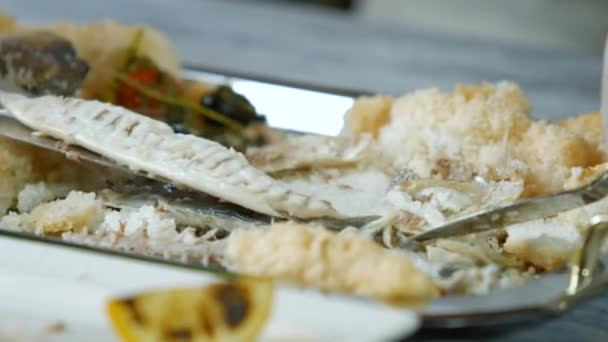 Spatula puts fish on plate.