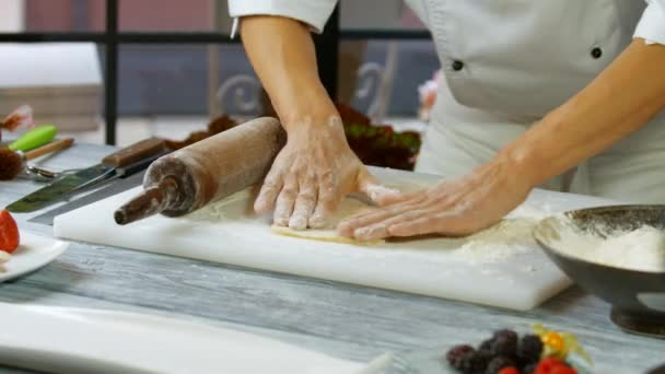 Male hands roll out dough.