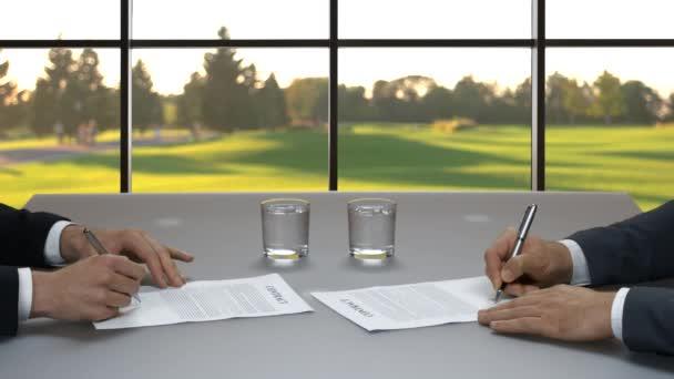 Men sign documents at desk.