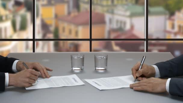 Men signing documents.
