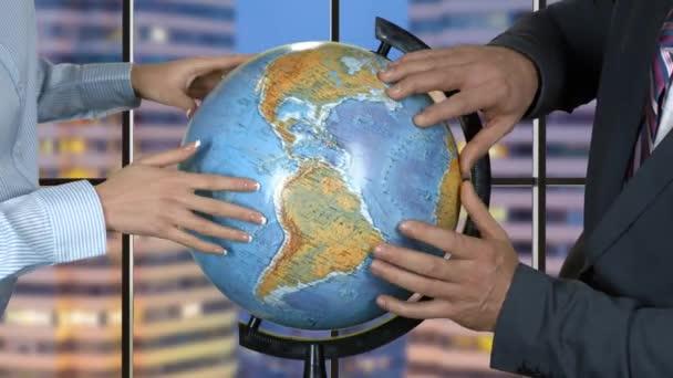 Mann und Frau berühren Globus.