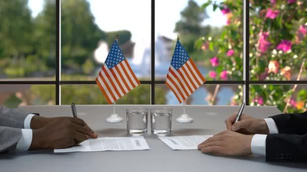 Men sign papers at desk.