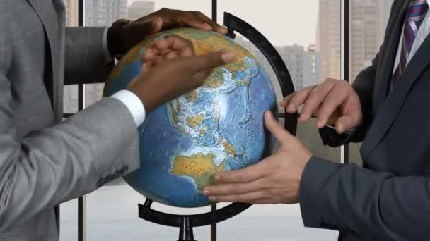 Businessmen touching globe.