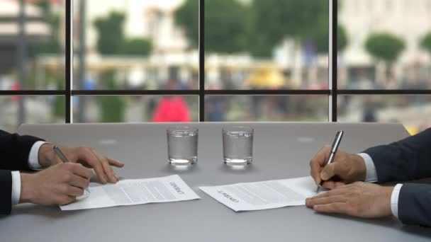 Two businessmen sign documents.