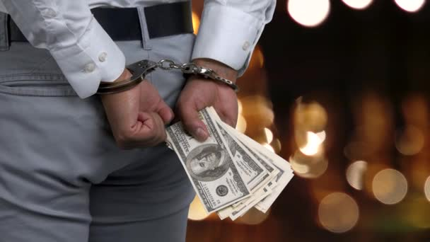 Side view man in handcuffs holding money.