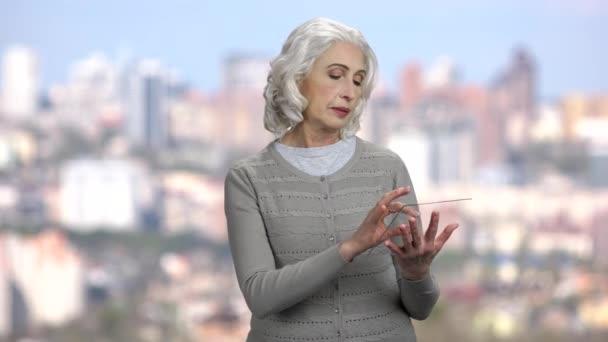 Reife Frau mit digitalem Tablet aus Glas.