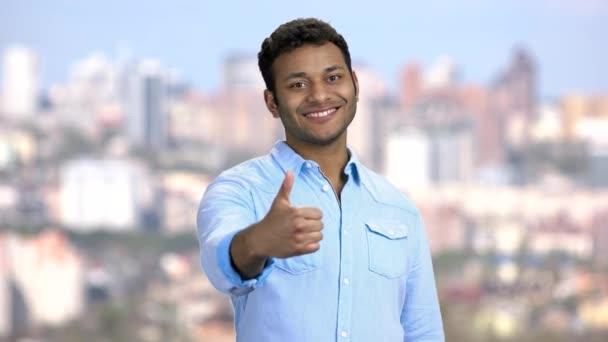 Fiatal mosolygós férfi mutatja hüvelykujját felfelé gesztus.