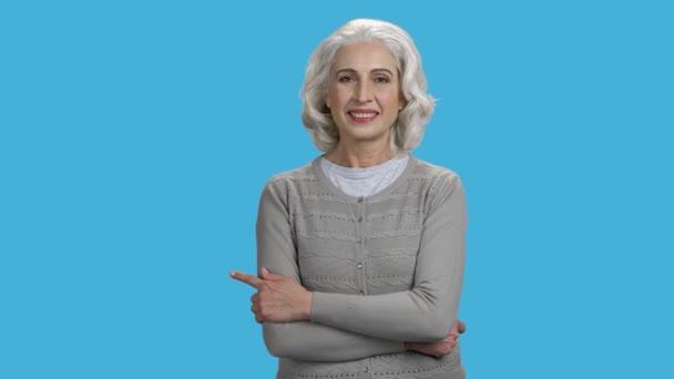 Usmívající se dospělá žena ukazuje prstem na kopírovací prostor.