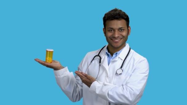 Lächelnder dunkelhäutiger Arzt zeigt Pillen auf farbigem Hintergrund.