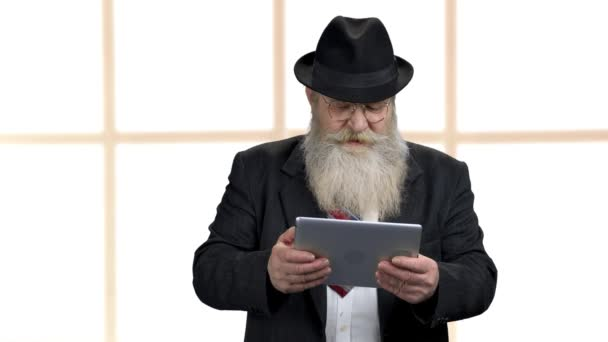Starší podnikatel hraje hru na tablet PC.