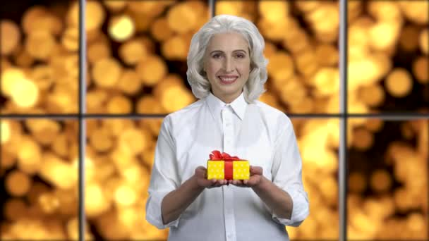 Smiling elegant business woman offering gift box.