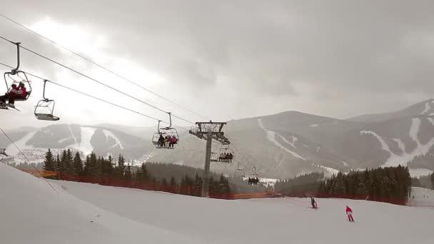 Skifahrer steigen am Sessellift auf.