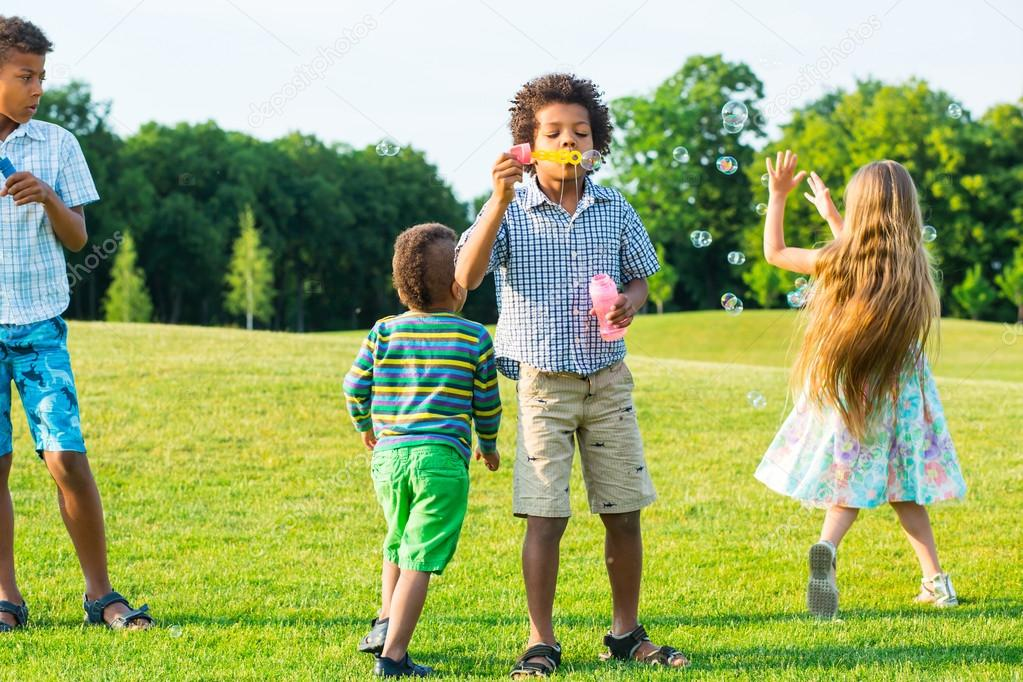 Four kids on glade with soap bubble.
