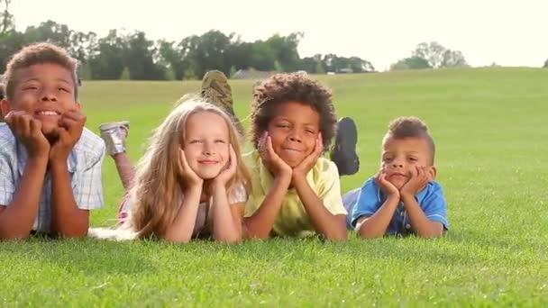 Four happy children on green grass.