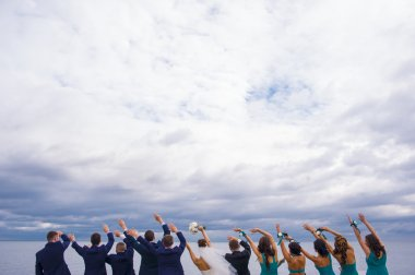 Guests on the wedding celebration are holding their hands up and