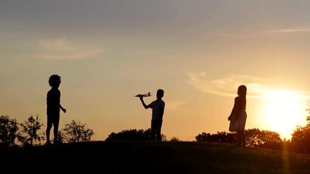Sagome di bambini sullo sfondo del tramonto