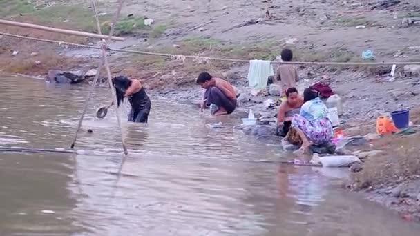 Lidé mytí a koupání v řece