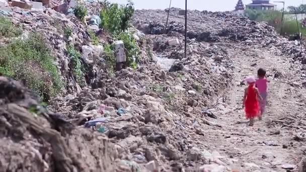 Little children walk on landfills.