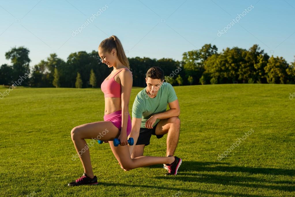 Trainer is engaged in fitness with girl on the nature.