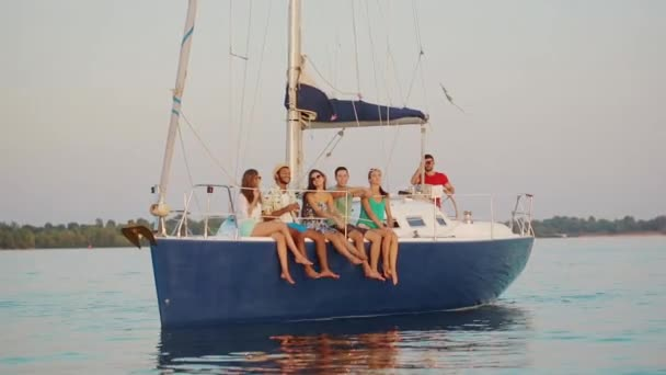 Happy young people sailing on the yacht