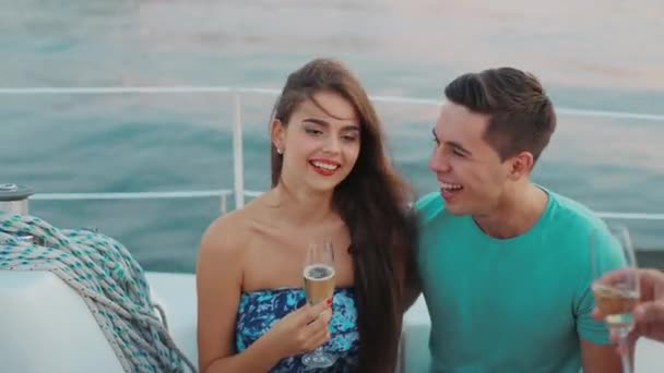 Boy and girl drink champagne on the yacht and having fun.