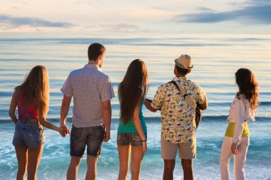 Guys and girls admire the view of the sea.