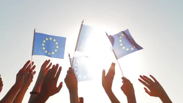 People with raised hands waving flags of the European Union.
