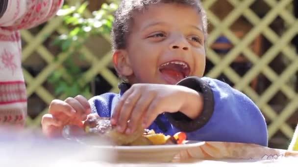 Happy child eats meat.