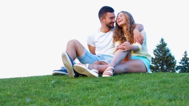 Lovers sit on the grass and hugging.