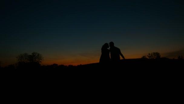 Lovers hugging on sunset background.