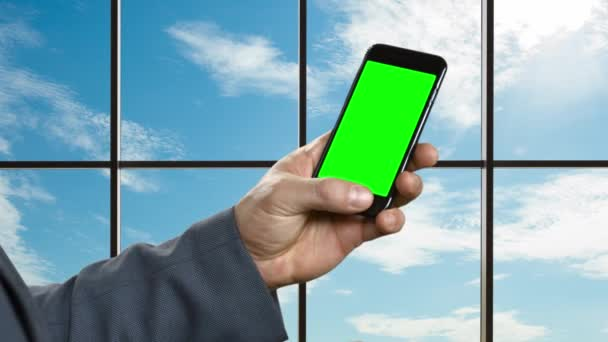 Man with smartphone on the background of a large window.