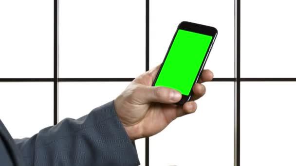 Businessman with a phone in skyscraper.