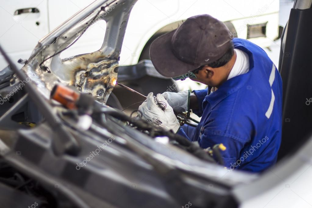 Man mechanical worker repairing a car body in a garage - Safety at work with protection wear. Welding work