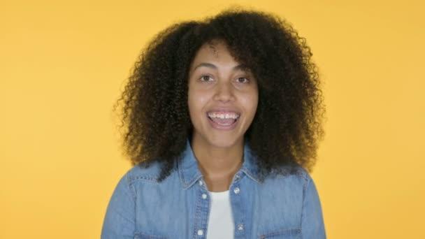 Junge Afrikanerin zeigt auf einladenden, gelben Hintergrund