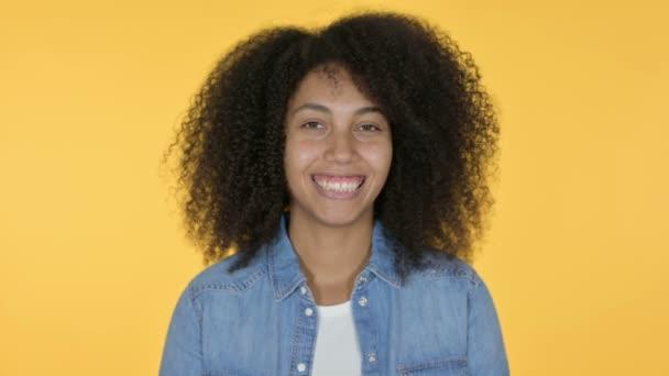Mladá africká žena s úsměvem na kameru, žluté pozadí