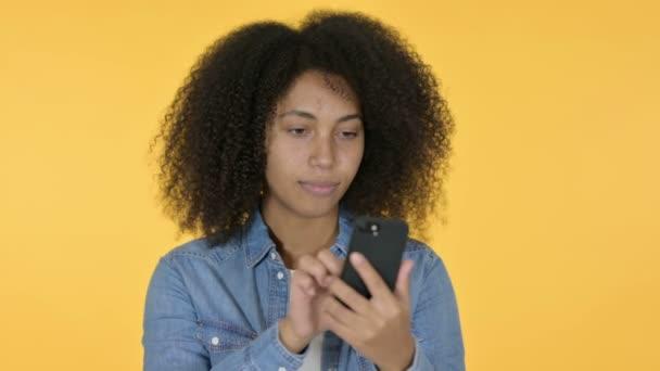Mladá africká žena slaví na Smartphone, žluté pozadí