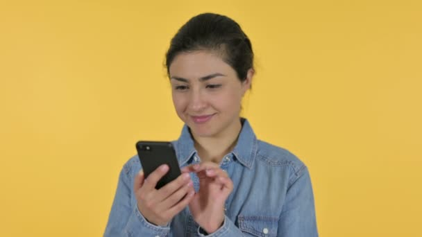 Junge Inderin feiert auf Smartphone, gelbem Hintergrund