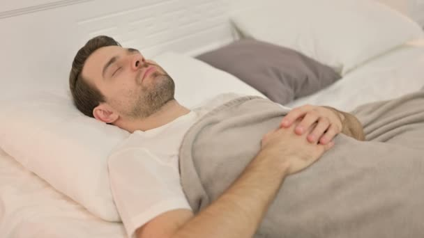 Békés fiatalember alszik az ágyban.