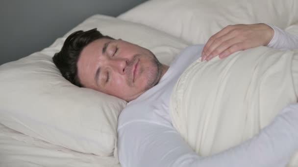 Klidný muž středověkého věku spí v posteli
