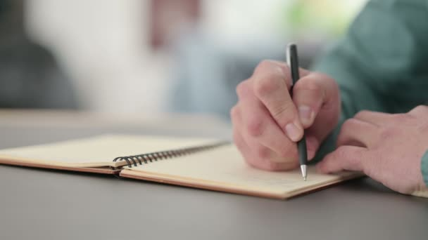 Close up of Hands of Man Writing in Notebook