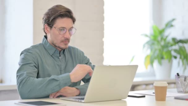 Middle Aged Man Thinking while using Laptop in Office
