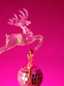 Weihnachtskarte mit Rentier-Spielzeug und sexy Mädchen auf rosa Hintergrund