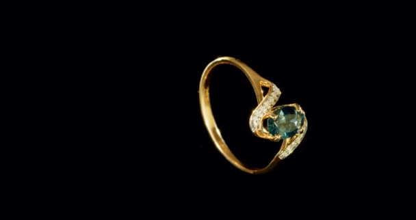 žlutá zlatý prsten s jeden velký modrý drahých kamenů uprostřed a dva řádky curlingu malých diamantů
