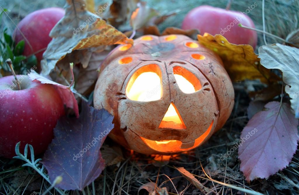 Candlestick pumpkin with a burning candle inside, among autumn fallen leaves and red apples, symbol of Halloween